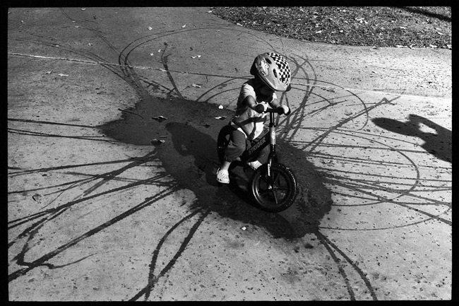 Roll-17-Kid-on-Bike-in-Puddle-Tavis-Leaf-Glover